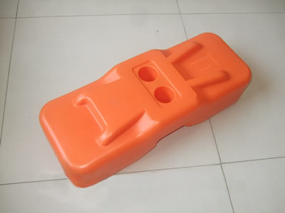An orange color plastic feet on the floor.